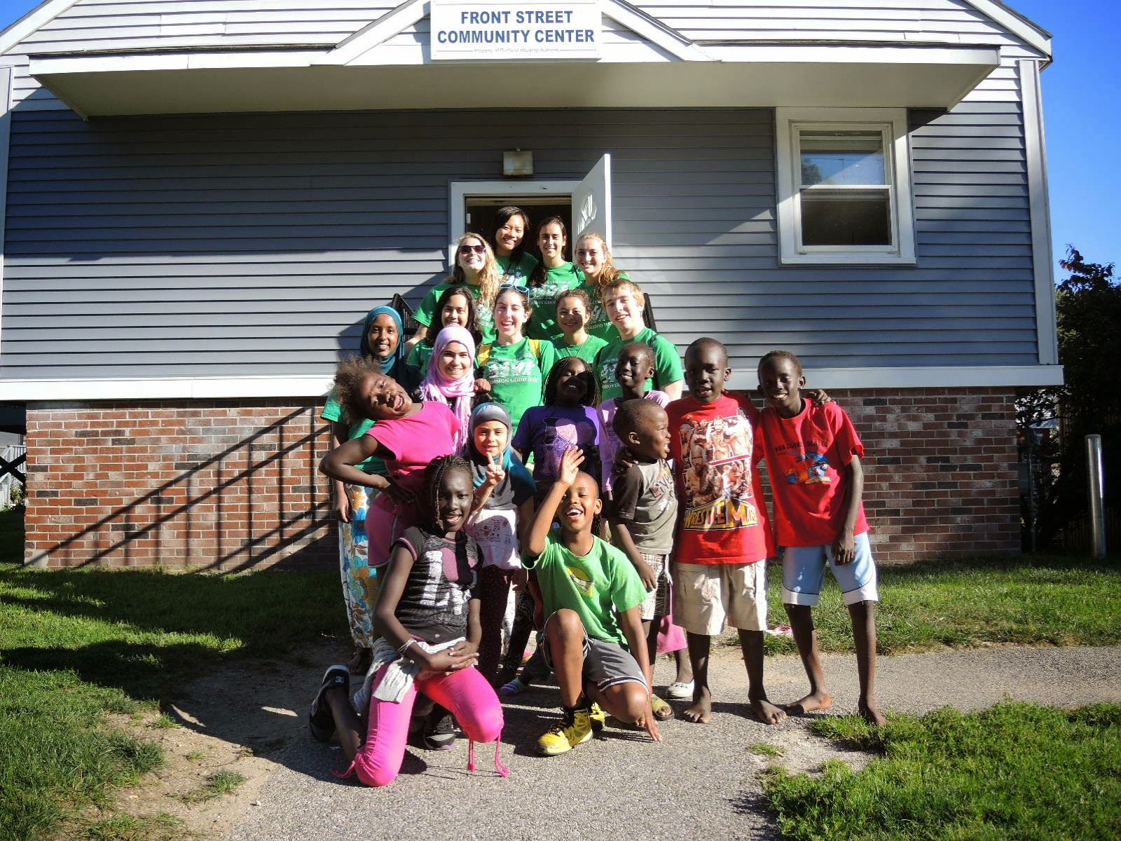 Youth from Front Street pose with volunteers in front of the Community Building